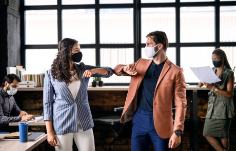 Young businesspeople with face masks working indoors in office, greeting.