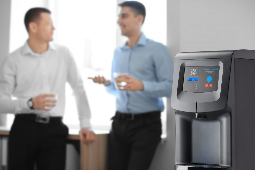 Team members talking behind a water cooler at the office