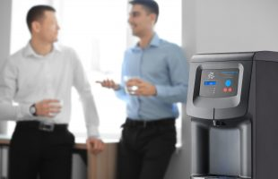 Office employees having break near water cooler