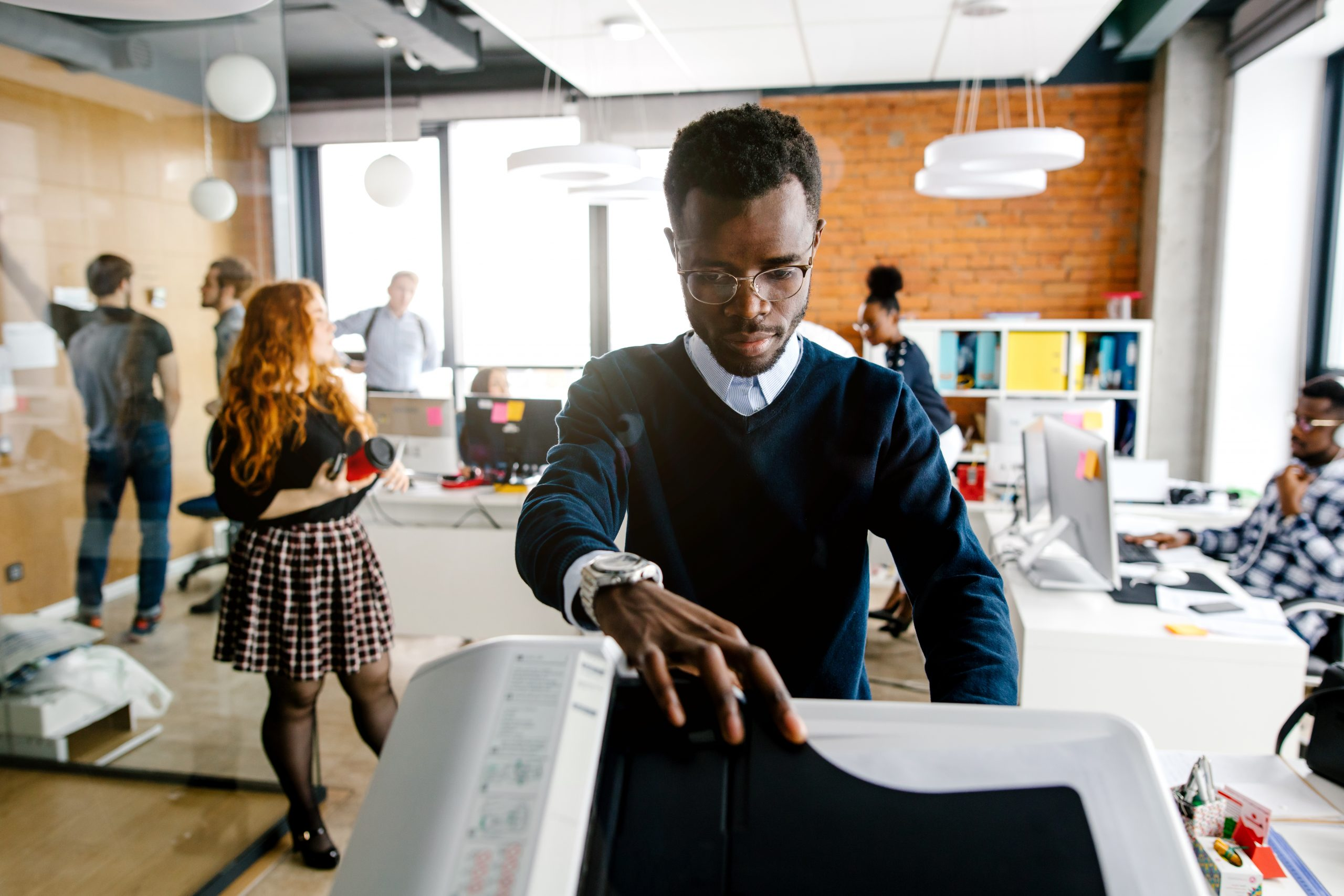 black worker is printing a file , document in the office room. Accounting concept