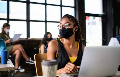 Portrait of young businesswoman with face mask working indoors in office.