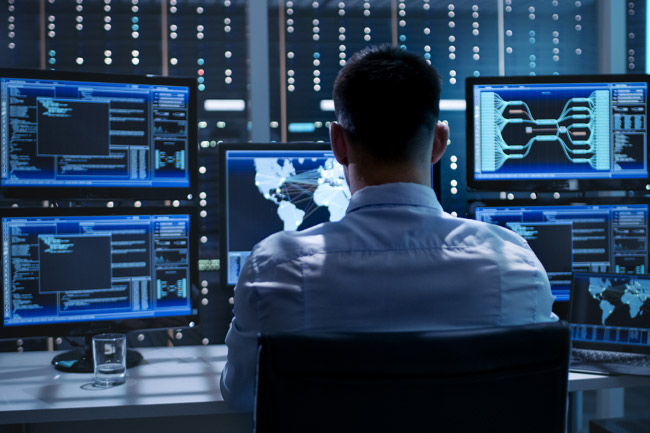 a man remotely monitoring systems and networks as part of managed cybersecurity