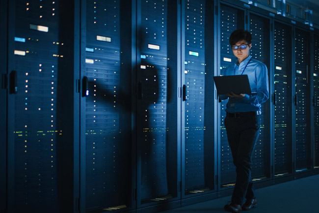 a woman in a server room to represent the importance of server availability for managed cybersecurity services