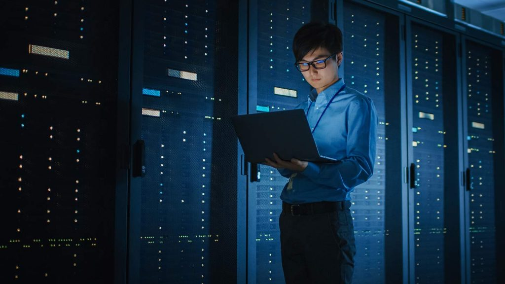 A young man checks servers to ensure data is protected and the system optimized for disaster prevention as well as recovery