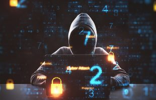 a hacker behind the laptop to represent ransomware attackers requesting payment in bitcoins
