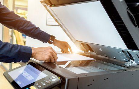 a man using an office copier to represent school office equipment