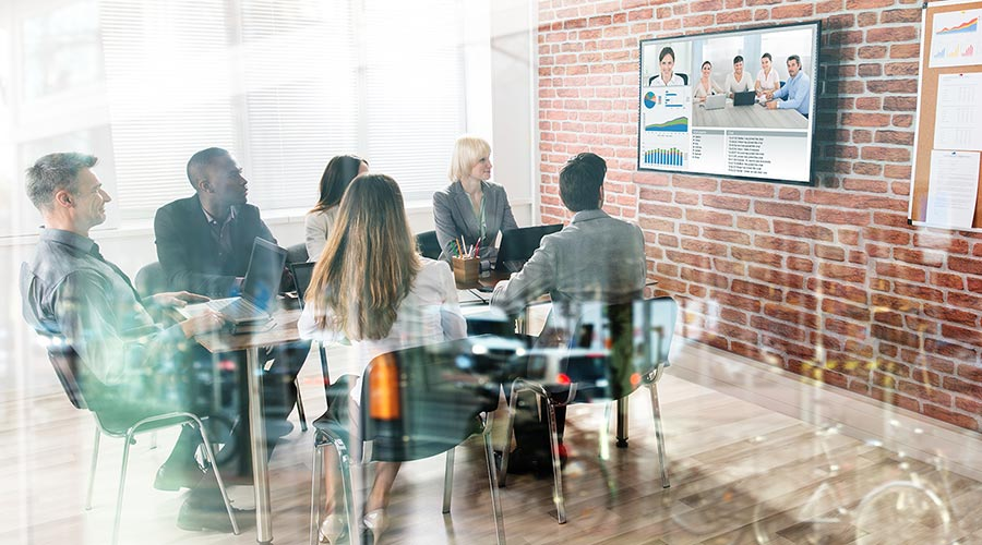 a team at the office and remote team members communicating via a video conferencing software