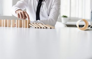 a man stopping the dominos from collapsing to illustrate what is business continuity