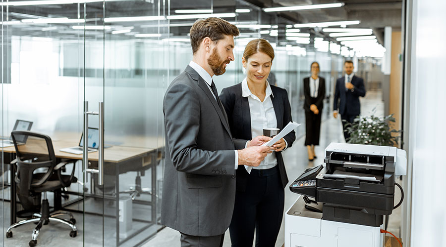 Two co-workers using a printer in office environment
