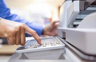 Printer brands: a man operating an office printer