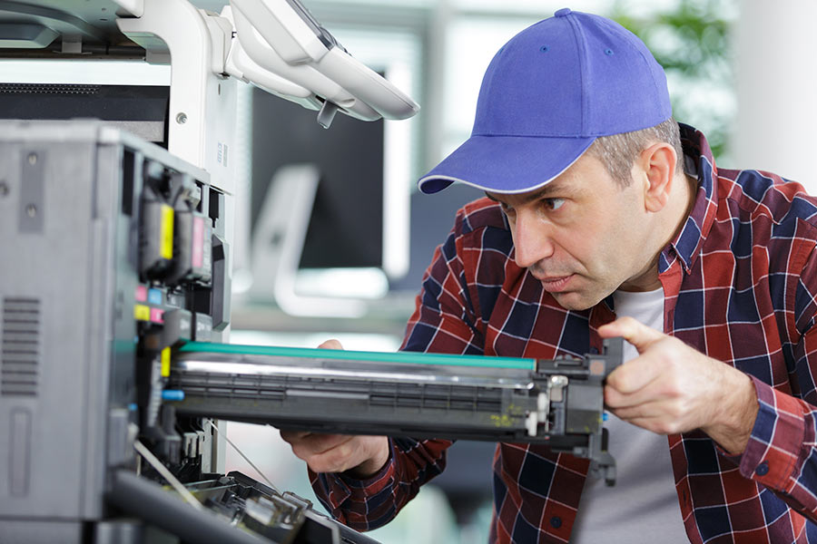 Man changing the ink cartridge of a leased copier