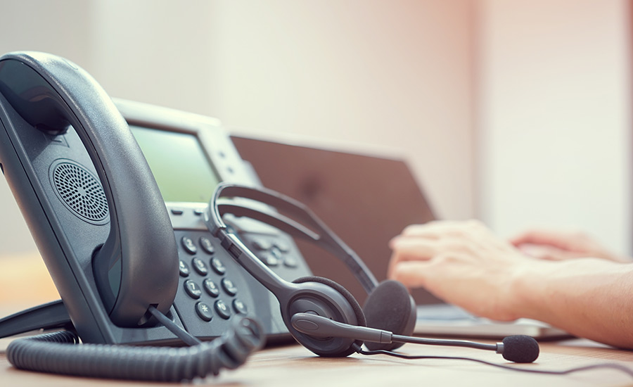 A desk phone with a headset next to it — elements of a VoIP solution